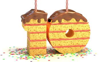 Ein Kuchen in Form einer Zehn steht auf einem mit Konfetti bestreutem Untergrund. Zwei Kerzen stecken darin.