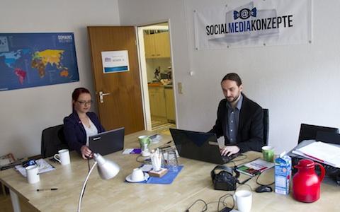 Das Büro von Social Media Konzepte. Am Schreibtisch arbeitet das Gründerpaar bestehend aus Anja Diestelrath und René Bogdanski an Laptops.