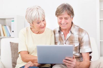 Ein älteres Paar sitzt auf der Couch und benutzt einen Laptop.