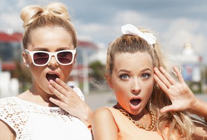 Zwei junge Frauen schauen sehr überrascht in die Kamera.