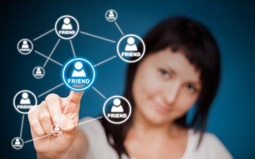 Im Vordergrund erscheint eine Netzwerkstruktur von unbenannten Freunden. Im Hintergrund ist eine Frau, die mit ihrem FInger auf einen Freund in diesem Netzwerk zu klicken scheint.