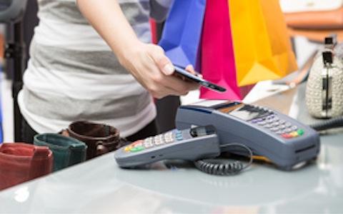 Eine Frauenhand hält ein Smartphone an ein Ec-Karten-Lesegerät.
