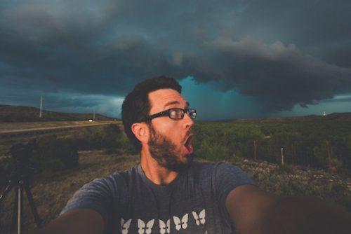 Ein Mann schaut überrascht über seine Schulter nach hinten. Es braut sich ein Sturm im Hintergrund zusammen.