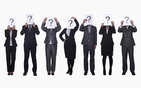 Sieben Personen in Businesskleidung halten sich selbst Zettel mit Fragezeichen vor ihr Gesicht.