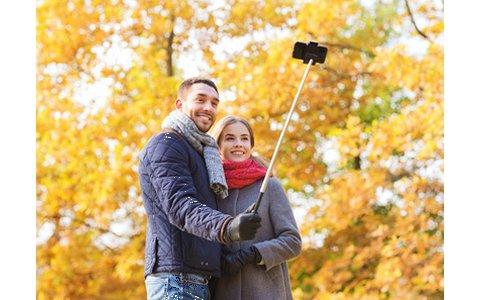 Ein Pärchen nimmt ein Selfie mit einem Selfiestick vor einem gelben Laubbaum auf.