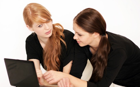 Zwei Frauen schauen irritiert auf einen Laptop.