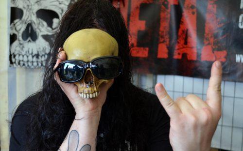 Ein Mann hält sich einen Totelschädel mit Sonnenbrille vor das Gesicht.