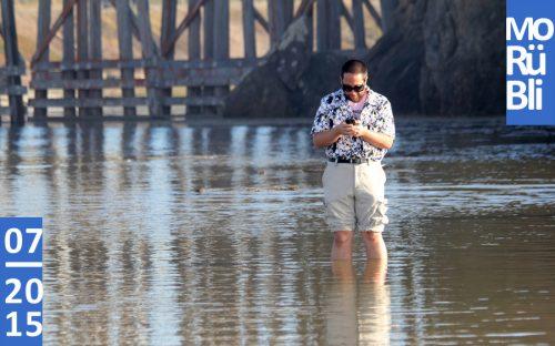 Ein angezogener Mann steht mit den Beinen im Wasser. Er schaut auf sein Handy.
