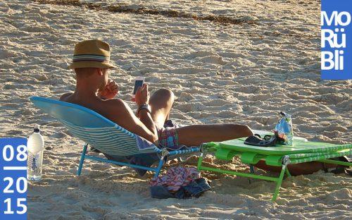 Ein Mann mit Hut liegt in Badehose auf einer Liege am Strand und schaut in sein Smartphone