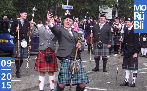Eine Parade mit Männern im Schottenrock. Im Vordergrund machen zwei Männer ein Selfie.