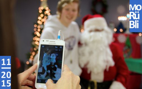 Eine Person fotografiert ein Kind, das auf dem Schoß des Weihnachtsmanns sitzt.