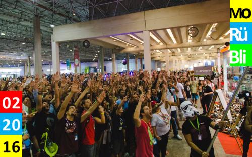 Viele Menschen stehen in einer Halle, heben die Arme und rufen.