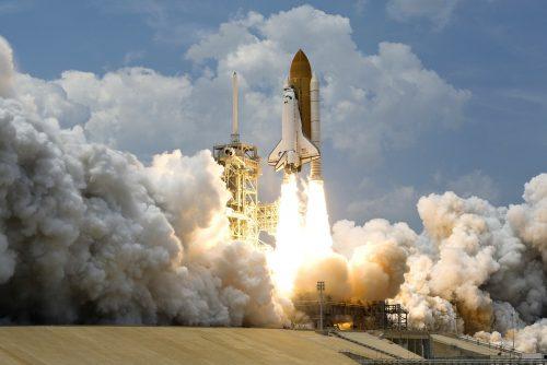 Fotografie eines Raketenstarts. Die Rakete hebt gerade ab und ist umgeben von Feuer und Qualm.