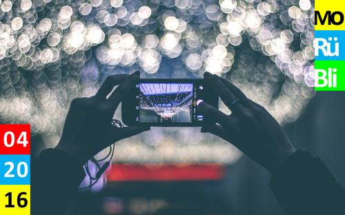 Zwei Hände halten ein Smartphone und fotografieren eine Decke aus Lichtern, die man verschwommen im Hintergrund erkennt.