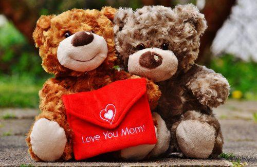 """Zwei Teddys halten einen roten Umschlag auf dem """"Love You Mom"""" steht."""