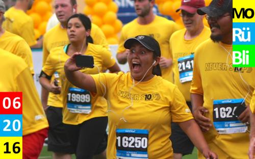 Menschen mit gelben Shirts bei einem Lauf. Eine Frau im Vordergrund macht ein Selfie und zieht dabei eine Grimasse.
