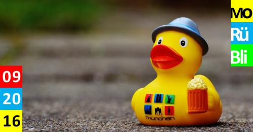 """Eine Quietsche-Ente mit Hut und Bier steht auf einem Weg. Auf ihrem Bauch steht """"München""""."""