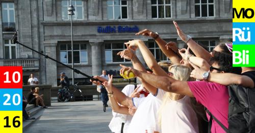 Mehrere Personen machen als Gruppe ein Foto von sich mit einem Selfiestick.