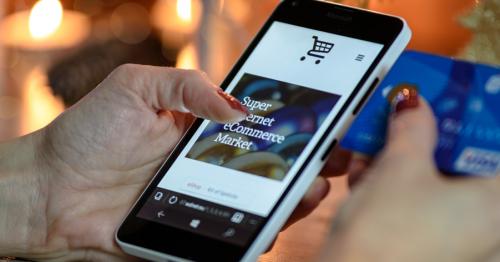 Eine Frau shoppt online. In der linken Hand hält sie ein Smartphone, in der rechten eine Kreditkarte.