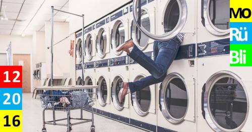 In einem Waschsalon stehen mehrere Waschmaschinen neben- und übereinander aufgereiht. Eine Frau steckt halb in einer der oberen Maschinen, um etwas herauszuholen. Beine und Füße hängen heraus in der Luft.