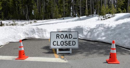 """Eine eingeschneite Straße wird durch zwei Verkehrshüte und ein Schild auf dem """"Road Closed"""" steht abgesperrt."""