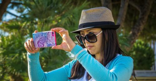Eine Frau mit Hut und Sonnenbrille nimmt ein Foto mit ihrem Smartphone auf.