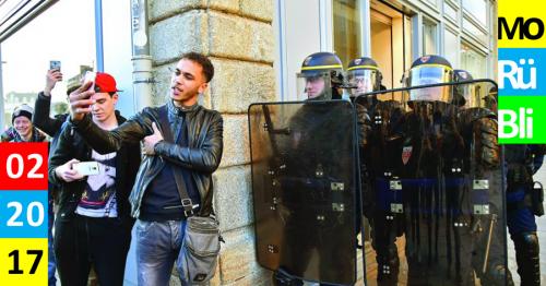 An einer Häuserecke stehen links junge Männer die Selfies machen und rechts POlizisten in Uniform mit Helmen und Schutzschilden.