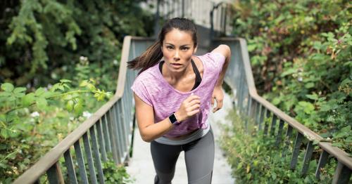 Eine Frau in Sportkleidung läuft den Betrachtenden entgegen eine Treppe hinauf. Sie trägt einen Fitness-Tracker am Handgelenk.