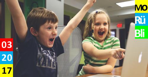Ein Mädchen und ein Junge vor einem iMac sind begeistert. Sie zeigt auf den Bildschirm und er reißt die Arme in die Höhe.