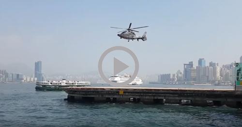 Ein Hafen über dem ein Helikopter fliegt. Im Vordergrund ist das Play-Symbol von Youtube eingeblendet.