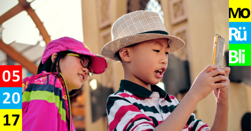Ein kleiner Junge mit Hut und Poloshirt steht auf einem Platz in einer Stadt und sieht auf ein Handy. Ein Mädchen steht hinter ihm, guckt ihm über die Schulter und sieht auch auf das Handy.
