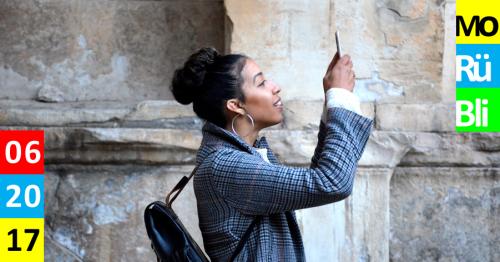 Eine dunkelhäutige Frau steht seitlich hebt das Smartphone und schießt ein Foto. Monatsrückblick.
