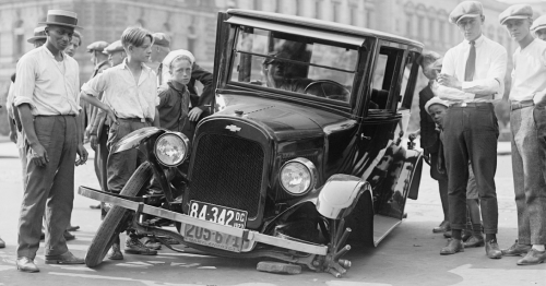 Eine schwraz weiß Fotografie eines Oldtimers, dem Reifen fehlen. Um das Auto herum stehen einige Männer und Jungen.