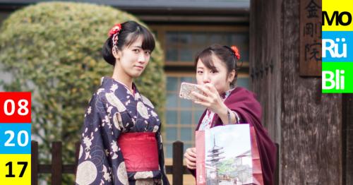 Zwei asiatische Frauen in Kimonos posen für ein Selfie vor einem Garten und einem Haus.