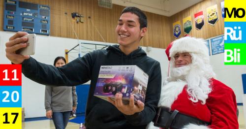 Ein Jugendlicher in einer Turnhalle macht ein Selfie mit einem Weihnachtsmann, während er eine VR Brille in der Hand hält.