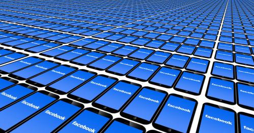 Viele schwarze iPhones liegen in Reihen. Auf allen Bildschirmen ist das Facebook Logo zu sehen.