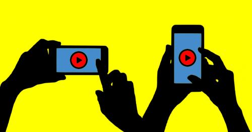 Zwei Handpaare halten jeweils ein Smartphone hoch auf denen der Play Button zum Schauen von Videos zu sehen ist.