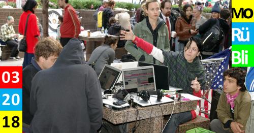 Mehrere Menschen sitzen draußen an einem Schachtisch und haben darauf ihre Laptops aufgebaut.