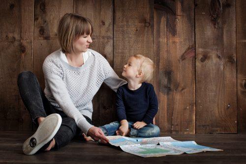 Mutter und Sohn sitzen nebeneinander auf dem Boden vor einer Holzwand. Sie sehen sich an und die Mutter zieht eine Grimasse. Vor ihnen liegt ein Stadtplan.