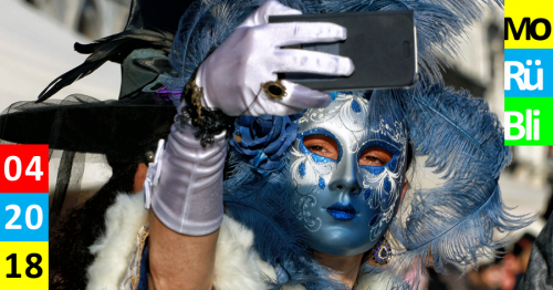 Eine Frau mit einer blau weißen Maske, die mit Federn geschmückt ist, macht ein Selfie.