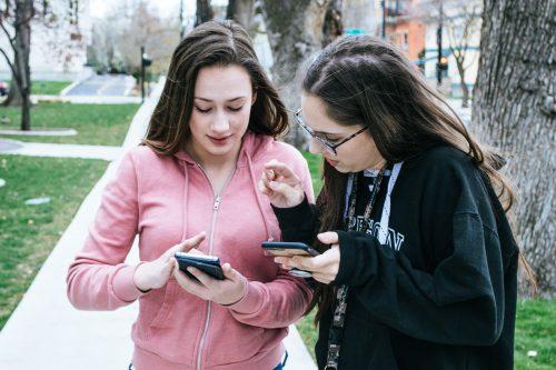Zwei jugendliche Mädchen stehen nebeneinander und halten Smartphones in den Händen. Beide schauen auf das Smartphone des linken Mädchens.