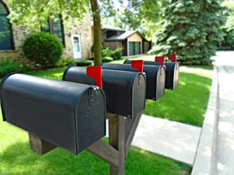 Vier Briefkästen mit aufgestelltem Brief-Fänchen im Vordergrund einer Reihe von Hauseinfahrten