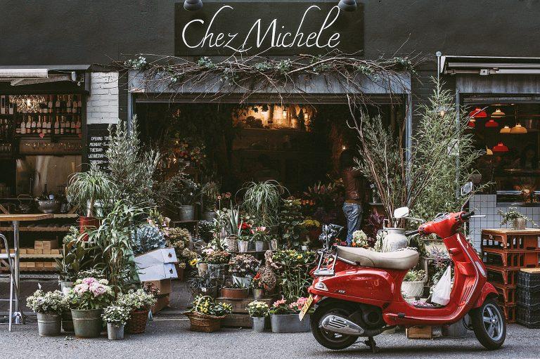 """Pflanzenladen mit vielen, gestapelten Topfpflanzen. Eine rote Vespa rechts. Schild """"Chez Michele""""."""