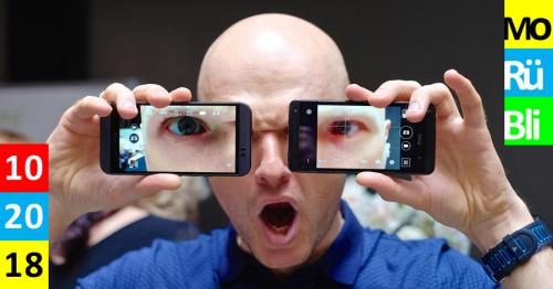 Glatzköpfiger Mann hält zwei Smartphones vor seine Augen, die vergößert werden. Monatsrückblick Oktober