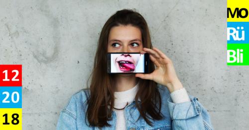 Junge Frau steht vor grauer Betonwand. Smartphone, mit Bild eines Mundes mit rausgestreckter Zunge ist vor ihrem Mund. Monatsrückblick