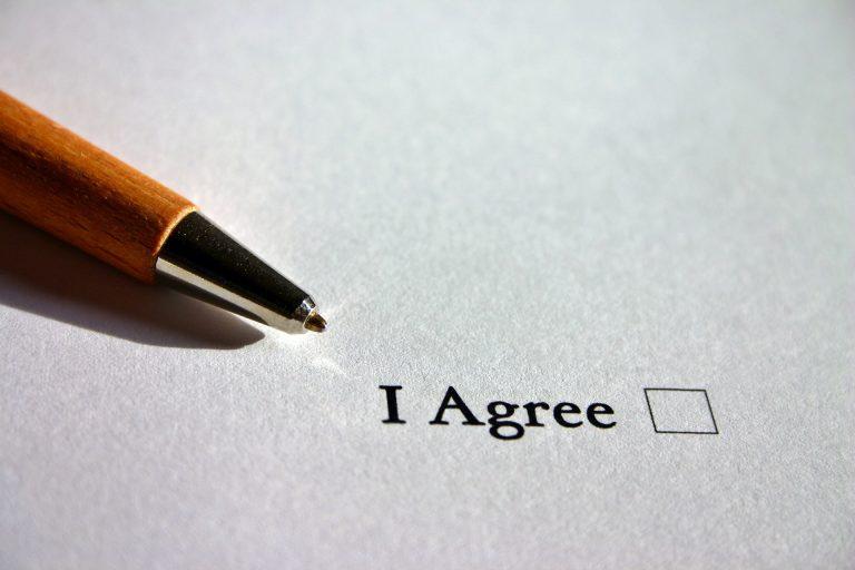 Weißes Blatt Papier. Ein Kästchen zum Ankreuzen mit den Worten I Agree. Daneben liegt ein geöffneter Kugelschreiber