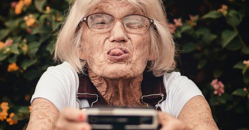 Alte Frau die in die Kamera guckt und Zunge rausstreckt Blog Influencer