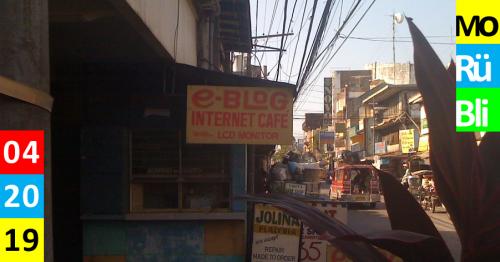 Eine heruntergekommene Straße mit vielen Menschen. An einem Shop an der Ecke hängt ein handbeschriebenes Schild mit den Worten e-blog Internet Café.