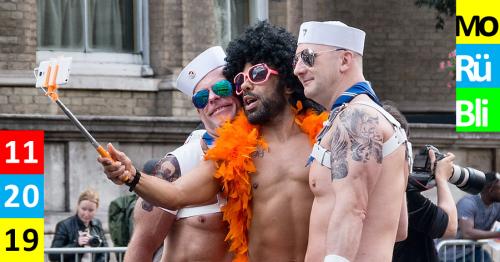 Drei oberkörperfreie, kostümierte Männer auf einer Parade. Sie umarmen sich und machen ein Foto mit einem Selfiestick.