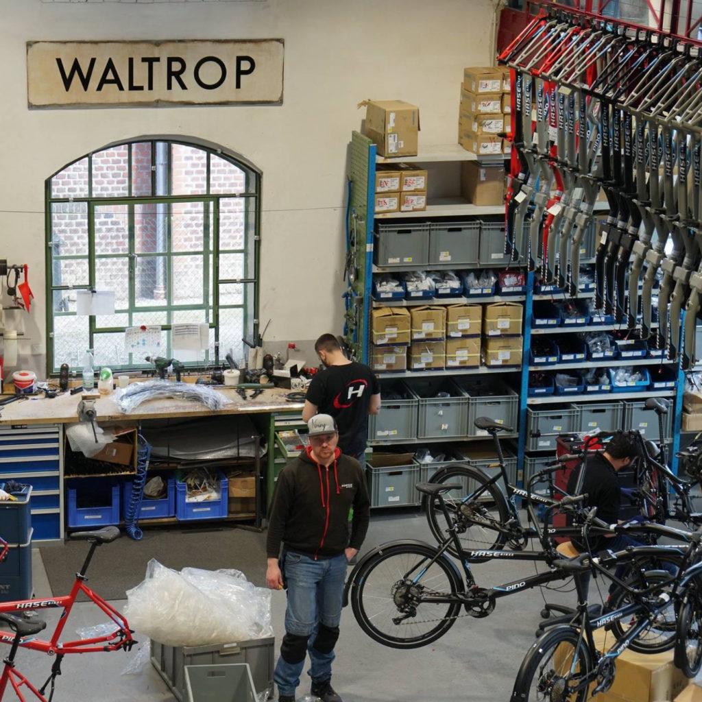 Zwei Männer arbeiten in einer Fahrradwerkstatt von Hase Bikes. In der Werkstatt hängen mehrere Fahrräder, Fahrradteile und ein Schild mit der Aufschrift Waltrop.